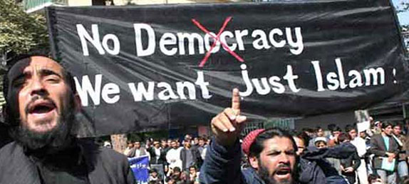 A crowd of Muslim men protesting with signs: No democracy, we just want Islam.