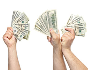 Four hands who have earned extra money hold up cash.