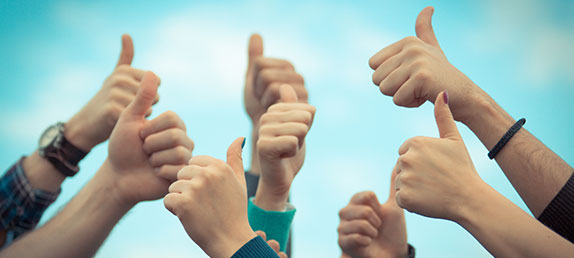 A group of hands with thumbs up with a lightly cloudy blue sky in the background. Inspire and enrich spiritual life.