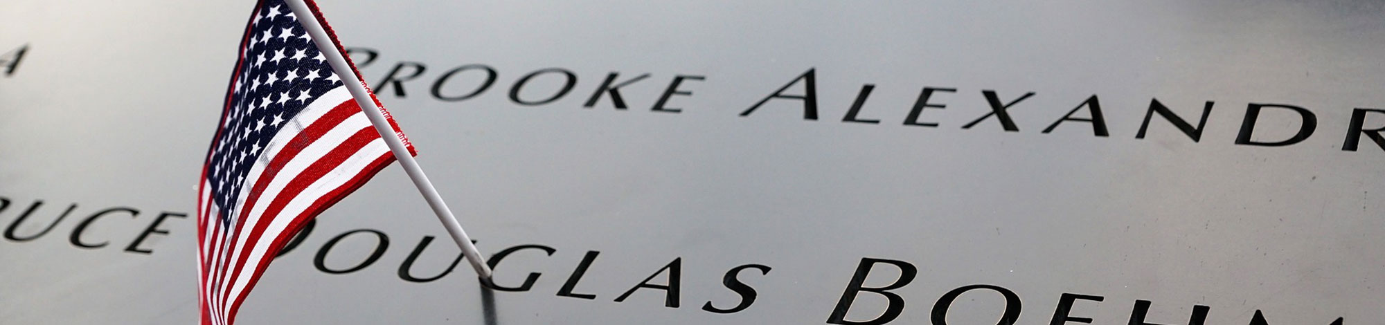 A close up of an American flag placed on the September 11th memorial with victims' names.
