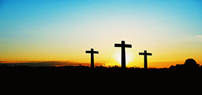 Three crosses on a grassy hill at sunset. Salvation comes only through Jesus Christ.
